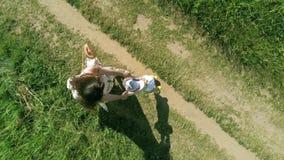 Tir aérien aérien de maman et de son peu d'enfant jouer ensemble et tourner autour des mains de participation photos stock
