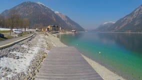 Tir aérien de quai en bois de lac, surface profonde de l'eau bleue, belles montagnes banque de vidéos