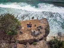Tir aérien des couples sur la falaise avec le fond d'océan photos libres de droits