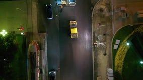Tir aérien des personnes travaillant la nuit pour étendre l'asphalte dans la ville, le trafic de voiture sur la route de côté banque de vidéos