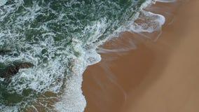 Tir aérien mobile lisse des ressacs bleus se brisant sur la plage sablonneuse d'or au Portugal banque de vidéos