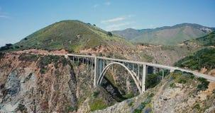 Tir aérien panoramique étonnant de stupéfier le pont et la route 1, point de repère célèbre en canyon de Bixby des Etats-Unis dan banque de vidéos