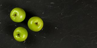 Tir aérien, trois pommes vertes sur le marbre noir comme le panneau, bannière large avec l'espace pour la droite des textes photo libre de droits