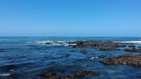 Tir aérien volant en avant au-dessus des roches et de l'océan sur la plage au Portugal banque de vidéos