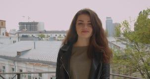 Tir arrière de la fille de brune dans la veste en cuir sur le balcon appréciant des tours urbanistiques de vue à la caméra et aux banque de vidéos