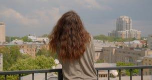 Tir arrière de modèle caucasien de brune sur le balcon appréciant la vue urbanistique ensoleillée banque de vidéos