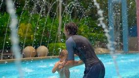 Tir au ralenti d'un jeune père et de son fils ayant l'amusement dans une piscine d'eau tropicale parmi des fontaines banque de vidéos