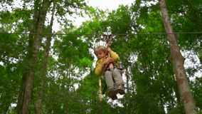 Tir au ralenti d'un petit garçon dans un harnais de sécurité sur un zipline dans les cimes d'arbre en parc d'aventure de forêt ex clips vidéos