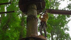 Tir au ralenti d'un petit garçon dans un harnais de sécurité sur un zipline dans les cimes d'arbre en parc d'aventure de forêt ex banque de vidéos