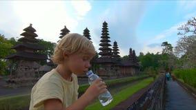 Tir au ralenti d'un petit garçon qui boit l'eau d'une bouteille en plastique se reposant sur un mur du temple de Taman Ayun banque de vidéos