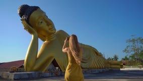 Tir au ralenti d'un voyageur de jeune femme visitant le le temple de Wat Srisoonthorn avec une statue du Bouddha menteur dessus banque de vidéos