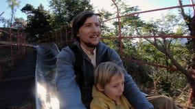 Tir au ralenti d'une équitation de père et de fils en bas des montagnes russes alpines dans une forêt d'automne clips vidéos