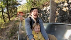 Tir au ralenti d'une équitation de père et de fils en bas des montagnes russes alpines dans une forêt d'automne banque de vidéos