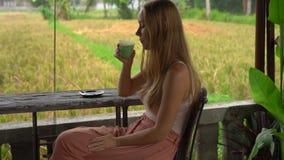Tir au ralenti d'une jeune femme buvant du latte de matcha de thé vert dans un café tropical avec la vue sur un gisement de riz banque de vidéos