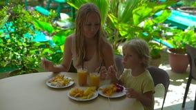 Tir au ralenti d'une jeune femme et de son fils mangeant un dîner de fruit dans un jardin tropical banque de vidéos