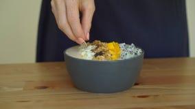 Tir au ralenti d'une jeune femme faisant cuire le bol de smoothie de banane avec le fruit du dragon, mangue, granola, raisin sec, banque de vidéos