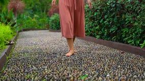 Tir au ralenti d'une jeune femme marchant sur un chemin réflexologique en parc tropical clips vidéos
