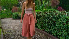 Tir au ralenti d'une jeune femme marchant sur un chemin réflexologique en parc tropical banque de vidéos
