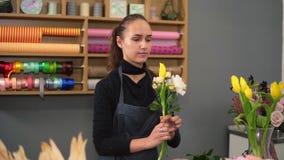 Tir au ralenti du jeune fleuriste féminin s'chargeant du bouquet moderne à la boutique de fleurs Elle combine les roses crémeuses banque de vidéos