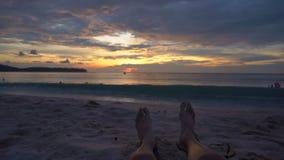 Tir au ralenti - jambes d'un homme sur une plage observant un coucher du soleil fantastique banque de vidéos