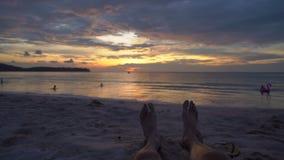 Tir au ralenti - jambes d'une femme sur une plage observant un coucher du soleil fantastique banque de vidéos