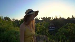 Tir au ralenti superbe d'une jeune femme dans une robe jaune marchant pendant le coucher du soleil à la promenade ou au peintre d banque de vidéos