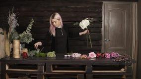 Tir avant impressionnant de fleuriste au travail Une gentille fille rassemble des fleurs dans une composition indoors banque de vidéos