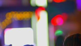 Tir brouillé des silhouettes des piétons fastly de marche sur égaliser le fond coloré de lumières de ville clips vidéos