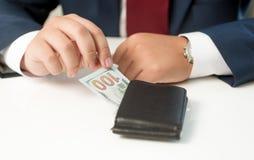 Tir conceptuel d'homme d'affaires prenant l'argent du portefeuille Photos stock