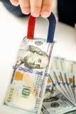 Tir conceptuel de fonctionnaire volant l'argent avec l'utilisation de l'aimant Images libres de droits