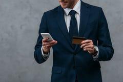 tir cultivé d'homme d'affaires avec la carte de crédit et le smartphone Images libres de droits