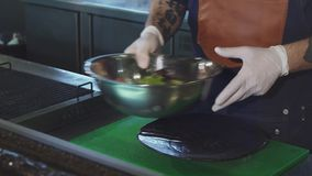 Tir cultivé d'un chef mettant la salade sur un plat clips vidéos