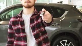 Tir cultivé d'un homme donnant des clés de voiture sur l'appareil-photo posant au concessionnaire clips vidéos