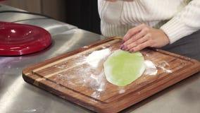 Tir cultivé d'une femme déroulant la pâte verte avec des herbes pour des pâtes clips vidéos