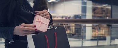 Tir cultivé d'une femme tenant peu de boîte-cadeau et le mettant dans faire des emplettes de retour au fond de mail Concept de l' photos libres de droits