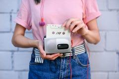 tir cultivé de femme avec des écouteurs tenant le rétro lecteur de cassettes et la cassette sonore dans des mains contre le blanc photos libres de droits
