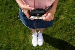 tir cultivé de femme avec des écouteurs tenant le rétro lecteur de cassettes avec la cassette sonore dans des mains tout en se te images libres de droits