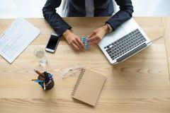 tir cultivé de femme d'affaires tenant des vitamines dans des mains sur le lieu de travail avec les dispositifs numériques images libres de droits