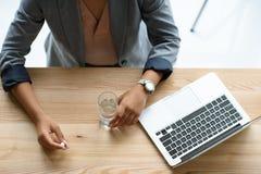 tir cultivé de femme d'affaires tenant la médecine et le verre de l'eau sur le lieu de travail Photo libre de droits