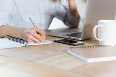 tir cultivé de femme d'affaires travaillant sur le lieu de travail avec les dispositifs numériques et les carnets photo stock