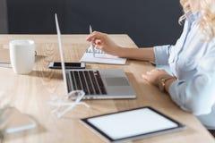 tir cultivé de femme d'affaires travaillant sur le lieu de travail avec les dispositifs numériques et les carnets image stock