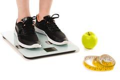 tir cultivé de femme se tenant sur des échelles avec la pomme et la bande de mesure se trouvant sur le plancher photos stock