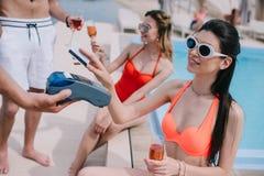 tir cultivé de fille de sourire payant avec la carte de crédit tout en buvant du champagne avec des amis image libre de droits
