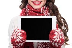 Tir cultivé de jeune femme de sourire dans l'écharpe et des mitaines montrant l'écran numérique de comprimé, photo stock
