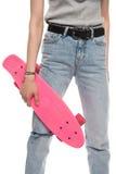 Tir cultivé de jeune femme tenant la planche à roulettes rose image stock