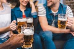 tir cultivé de jeunes amis tenant des verres de bière dans des mains Photos stock