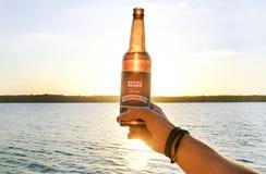 Tir cultivé de la main masculine tenant la bouteille à bière contre le coucher de soleil Fond du fleuve Mississippi Homme célébra Photographie stock