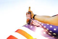 Tir cultivé de la main masculine tenant la bouteille à bière et le drapeau national des Etats-Unis contre le coucher de soleil Fo Photos libres de droits