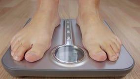 Tir cultivé de la pondération aux pieds nus d'homme sur l'échelle avec l'affichage clips vidéos