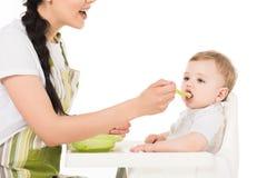 tir cultivé de mère alimentant peu de fils s'asseyant dans le highchair photo stock